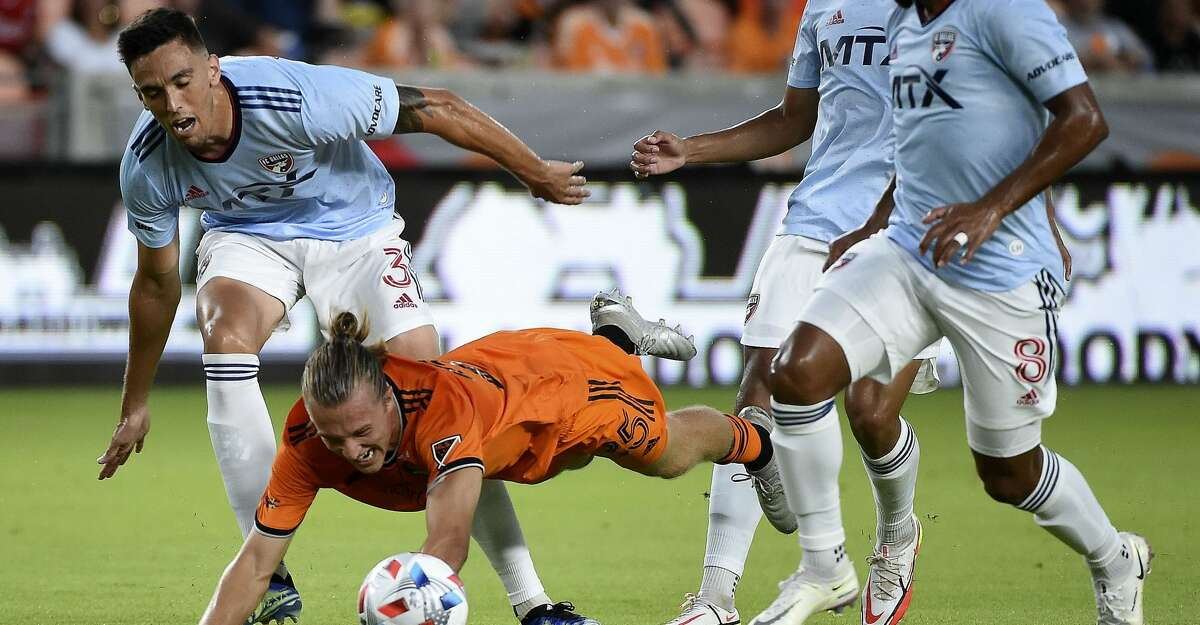 Houston Dynamo midfielder Griffin Dorsey, bottom, is tripped up by FC Dallas defender Jose Antonio Martinez, left, during the first half of an MLS soccer match, Saturday, Aug. 21, 2021, in Houston.