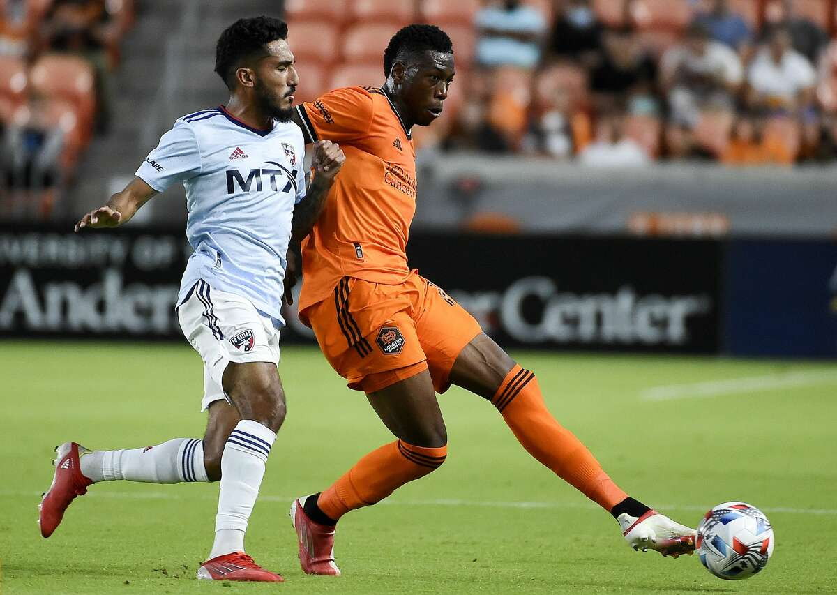 Houston Dynamo Teenage Hadebe, right, passes the ball as FC Dallas forward Jesus Ferreira defends during the first half of an MLS soccer match, Saturday, Aug. 21, 2021, in Houston.