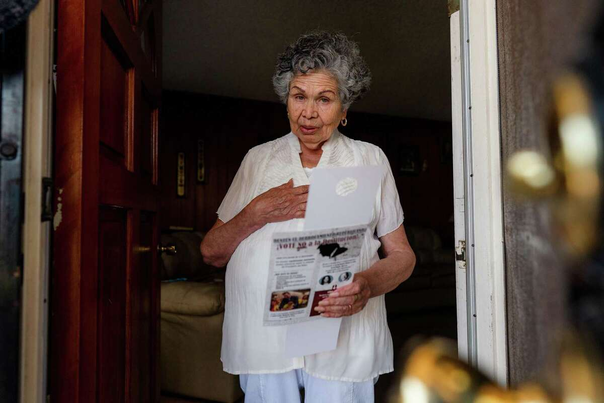 Concepción Aranda, 85, a retired health educator, stands inside the doorway of her Oakland home after speaking a volunteer canvasser asking her to vote no against the recall of Gov. Gavin Newsom.
