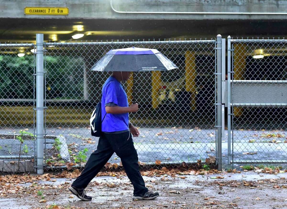 New Haven, Connecticut - Sunday, August 22, 2021: A pedestrian navigates the Park St. sidewalk in New Haven under the protection of an umbrella Sunday morning as Hurricane Henri dropped only rain in the greater New Haven area as it was downgraded to a tropical storm. Gov. Ned Lamont issued a travel ban on Interstate 95 late Saturday night in preparation for Tropical Storm Henri.