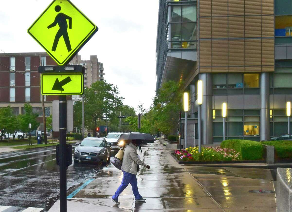 New Haven, Connecticut - Sunday, August 22, 2021: A pedestrian under the protection of an umbrella navigates the sidewalk in front of the Smilow Cancer Center in New Haven early Sunday morning as Hurricane Henri dropped only rain in the greater New Haven area as it was downgraded to a tropical storm.