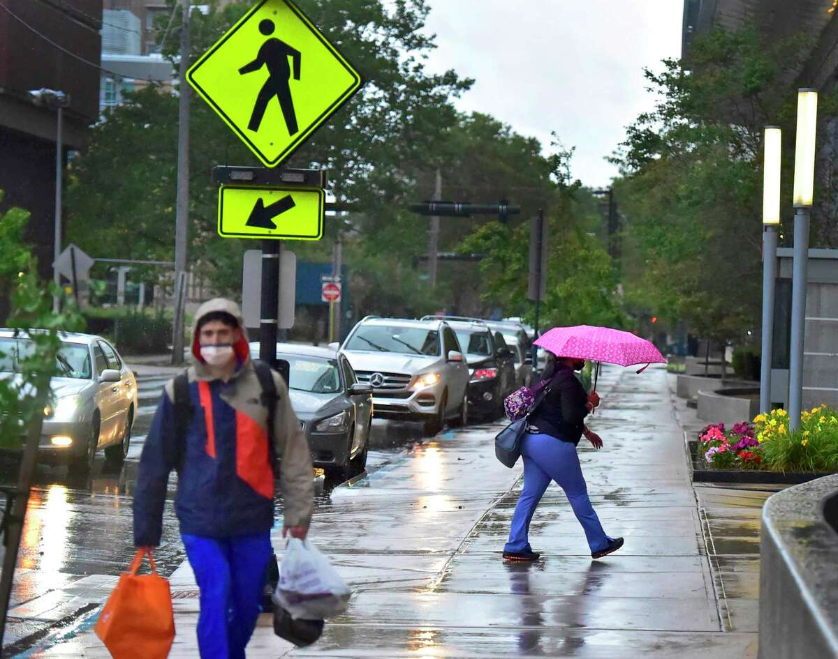 New Haven, Connecticut - Sunday, August 22, 2021: Pedestrians navigate the sidewalk in front of the Smilow Cancer Center in New Haven early Sunday morning as Hurricane Henri dropped only rain in the greater New Haven area.