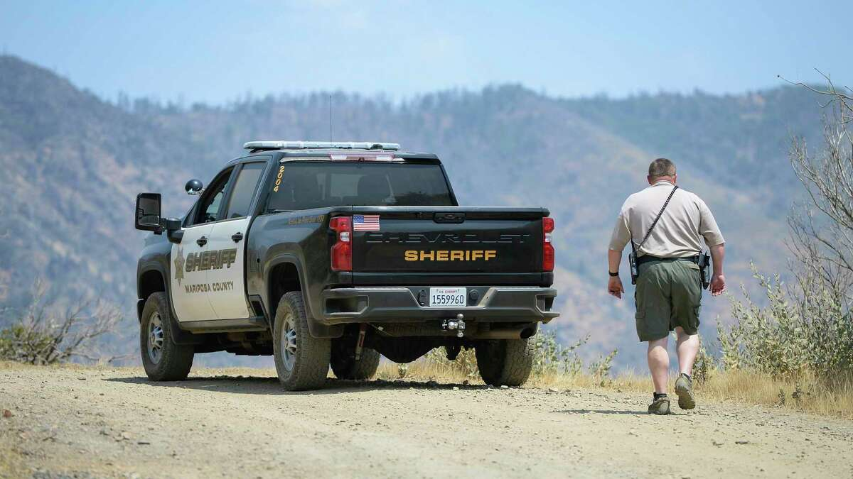 A Mariposa County deputy sheriff is standing guard over a remote area in the northeastern city of Mariposa, California, on Wednesday, August 18, 2021, near the area where a family and dogs were found dead the day before.  Investigators are considering whether toxic algae florx or other hazards may contribute to the deaths of the Northern California couple, their babies and the family dog on a remote hiking trail, authorities said.