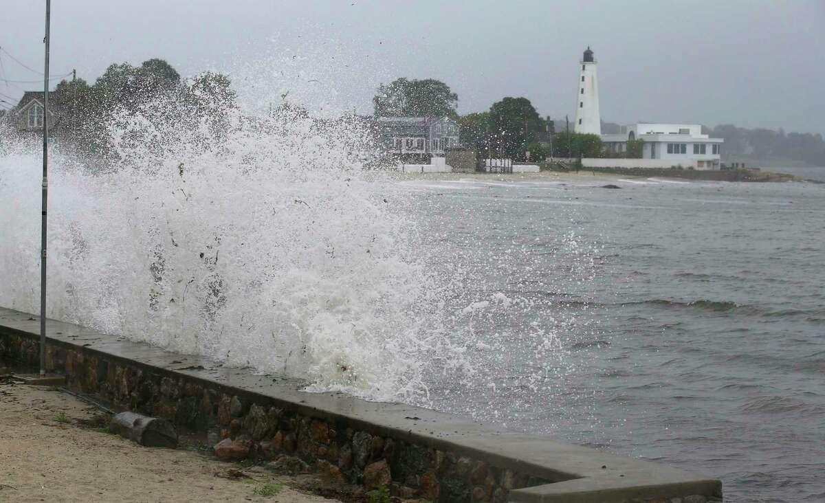Waves crash against the sea wall near New London Harbor Lighthouse as Tropical Storm Henri approaches Sunday, Aug. 22, 2021, in New London, Conn.
