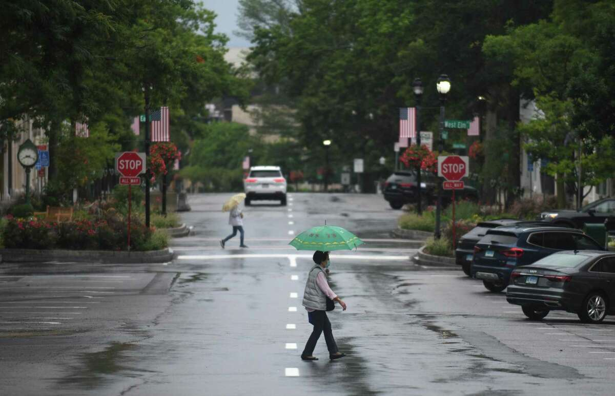 Folks take cover from the rain as Tropical Storm Henri hits Greenwich, Conn. Sunday, Aug. 22, 2021. Henri was downgraded from a hurricane to a tropical storm as the storm took a turn eastward before hitting land.