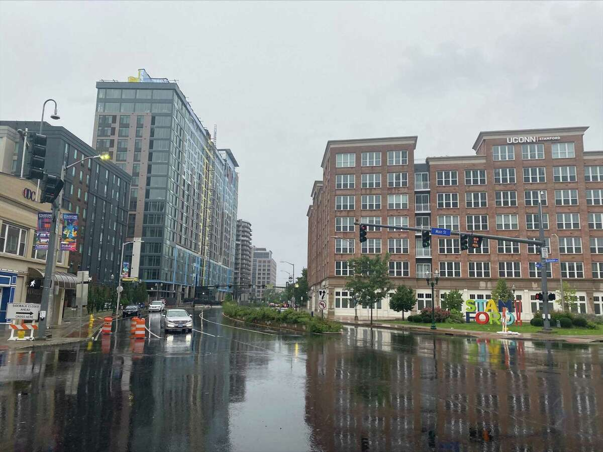 A car slowly drives in downtown Stamford the rain as Tropical Storm Henri hits on Sunday, Aug. 22, 2021. Henri was downgraded from a hurricane to a tropical storm as the storm took a turn eastward before hitting land.