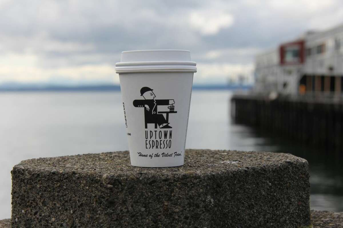 An Uptown Espresso coffee cup stands in front of Puget Sound.