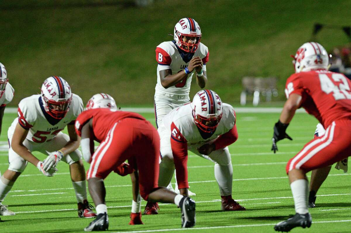 Kenneth Rosenthal (8) of Lamar takes a snap during the first half of a Class 6A Region III Division II area round football game between the Lamar Texans and the Katy Tigers on Friday, December 18, 2020 at Rhodes Stadium in Katy, Texas.