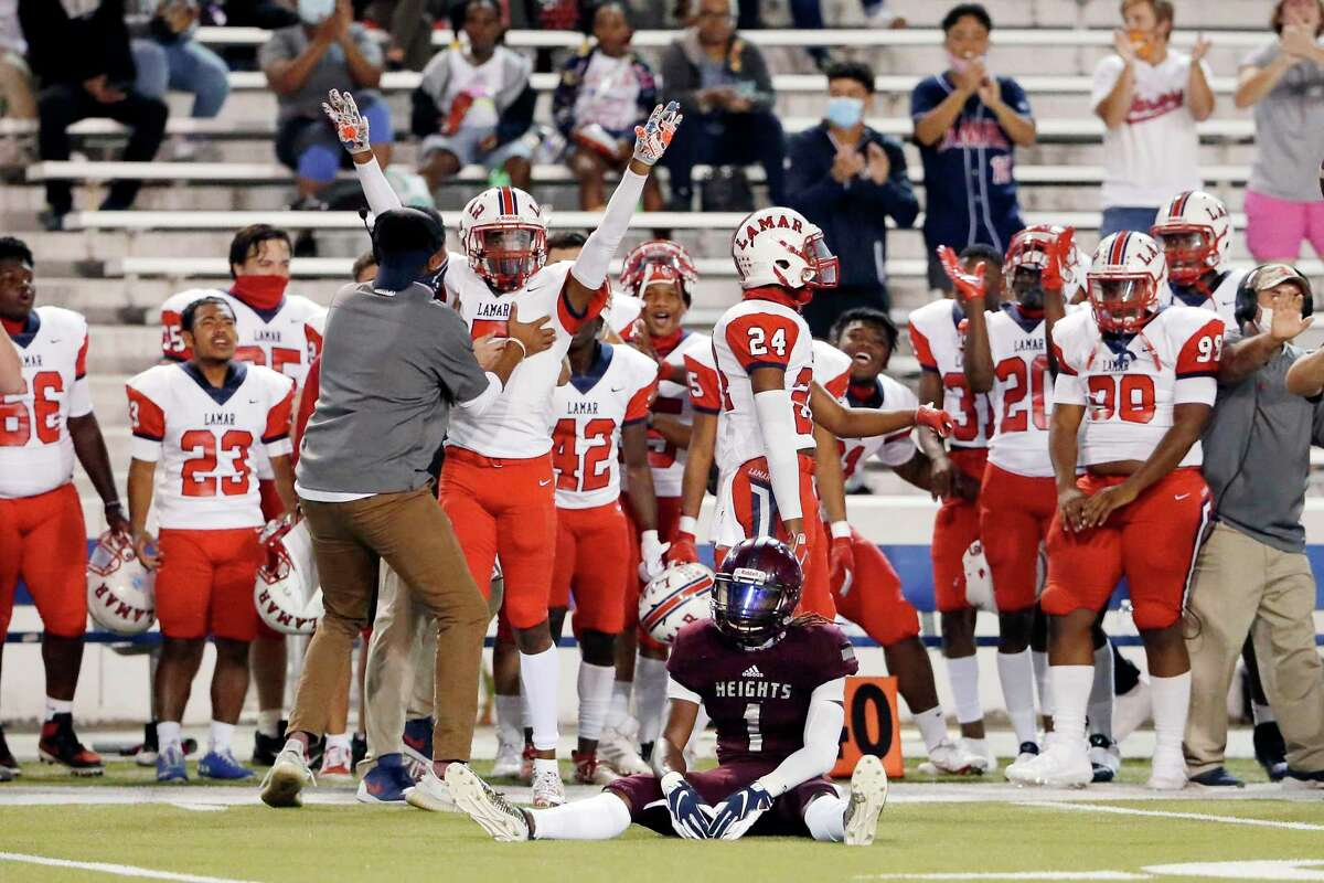 Heights Bulldogs receiver Kendrick Rhymes sits on the field as he reacts to having a pass knocked away by Lamar Texans Javion Green, with arms up, during the first half of a high school football game at Delmar Stadium Friday, Nov. 13, 2020 in Houston, Texas.