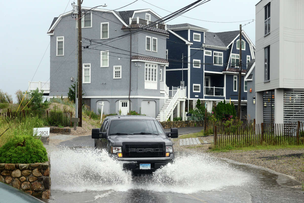 High tide brought the waters of Long Island Sound onto a short stretch of Fairfield Beach Rd., in Fairfield, Conn. Aug. 22, 2021. As Tropical Storm Henri passed farther to the east, most of coastal Fairfield County experienced an ordinary rainy day on Sunday.