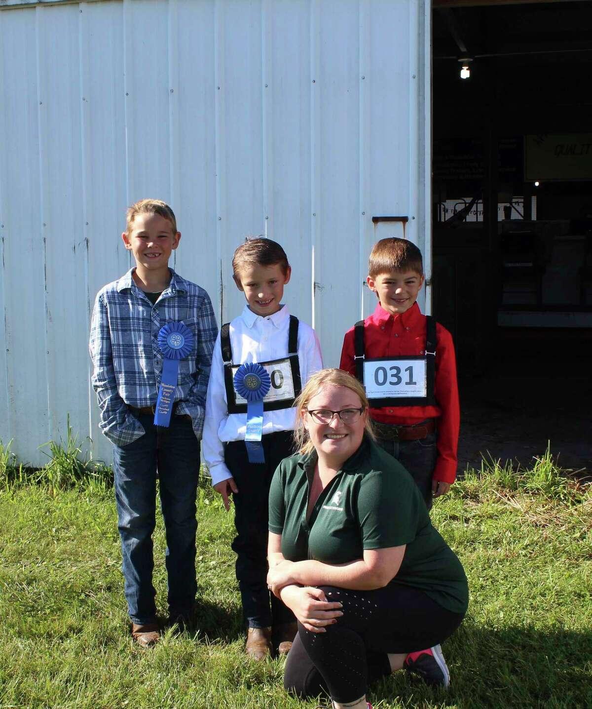 Lane Bradford, Kason Lambert, Sam Burrus and 4-H coordinator Allison Olson at the Manistee County Fair.(Kate Goodman/News Advocate)