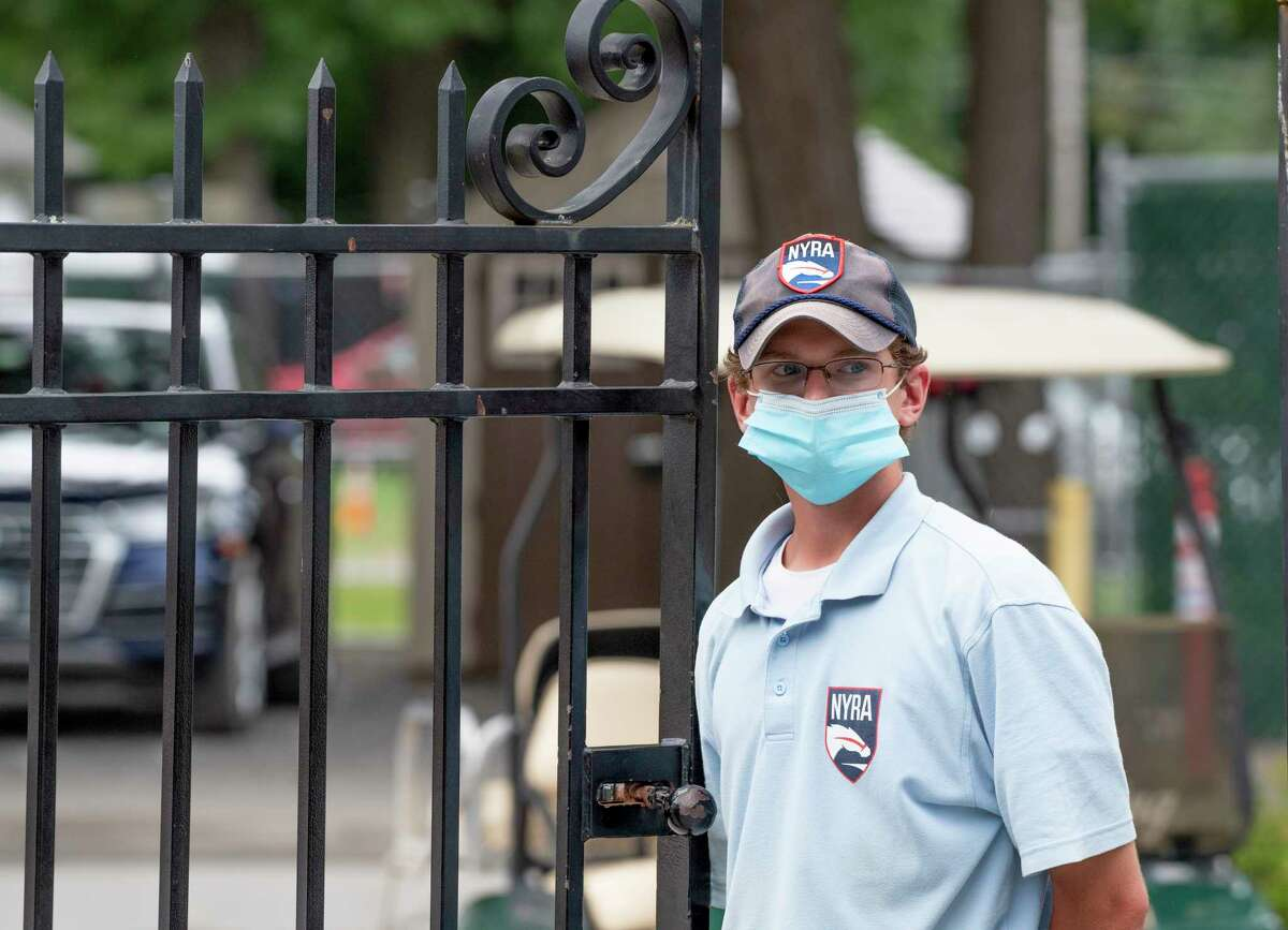 NYRA Security member Liam Dreyer wears a face mask as he works the entry gate near the Whitney entrance at the Saratoga Race Course on Sunday Aug 22, 2021.