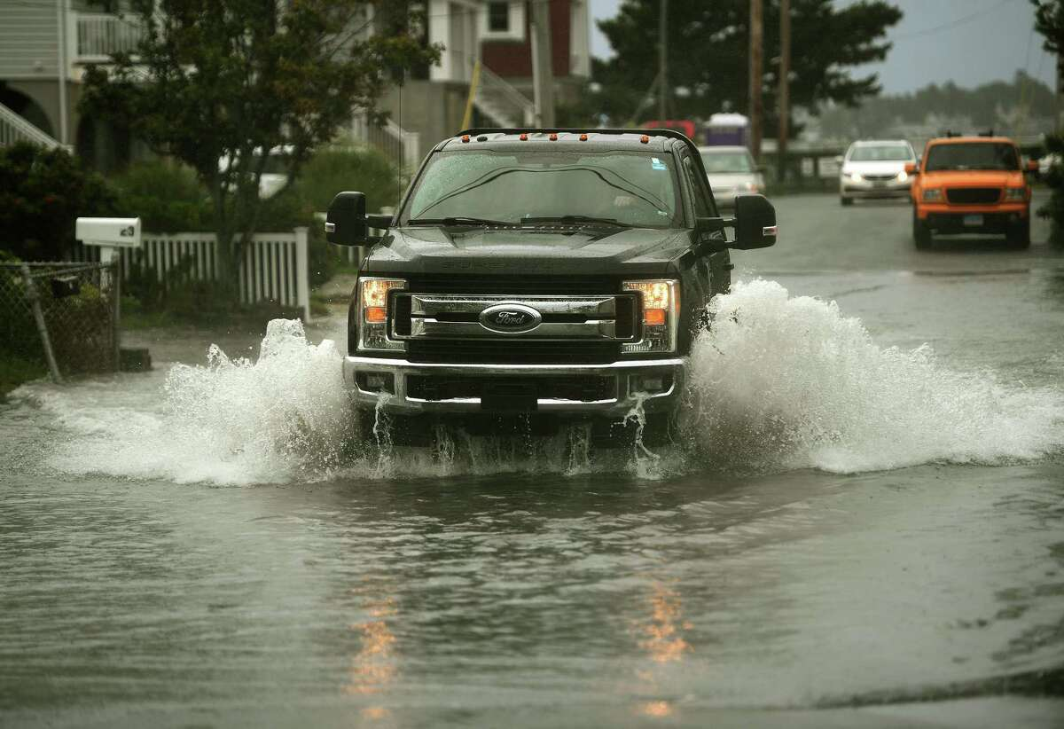 A pickup truck crosses a flooded section of Point Beach Drive during rains from Tropical Storm Henri in Milford, Conn. on Sunday, August 22, 2021.