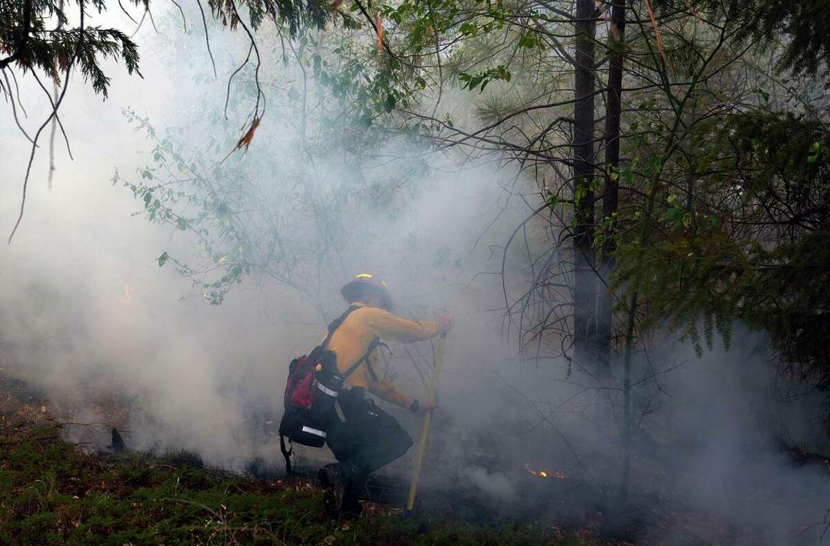 A crew member tackles spot fires from the Caldor blaze in El Dorado County. The fire forced closure of Highway 50, the main route to South Lake Tahoe.