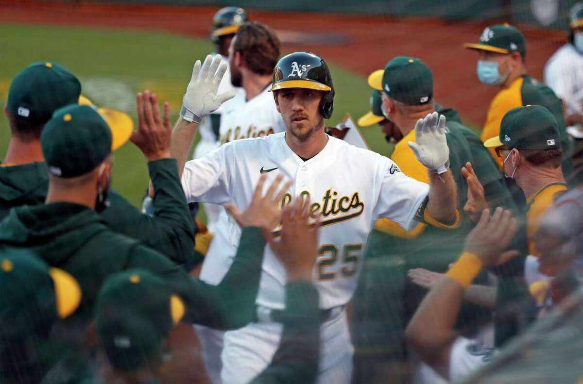 After hitting a 2-run home run, Oakland Athletics' Stephen Piscotty returns to dugout in 2nd inning against Toronto Blue Jays during MLB game at Oakland Coliseum in Oakland, Calif., on Monday, May 3, 2021.