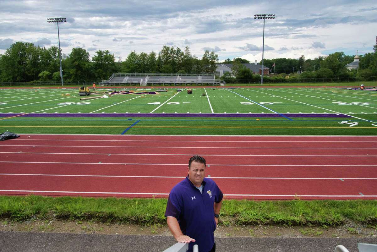 New CBA football coach Bobby Burns poses at the school's football field as a new turf field is being installed on Sunday, Aug. 22, 2021, in Colonie, N.Y. Burns went 58-4 in six seasons as Troy High's head coach before moving to the same post at CBA.