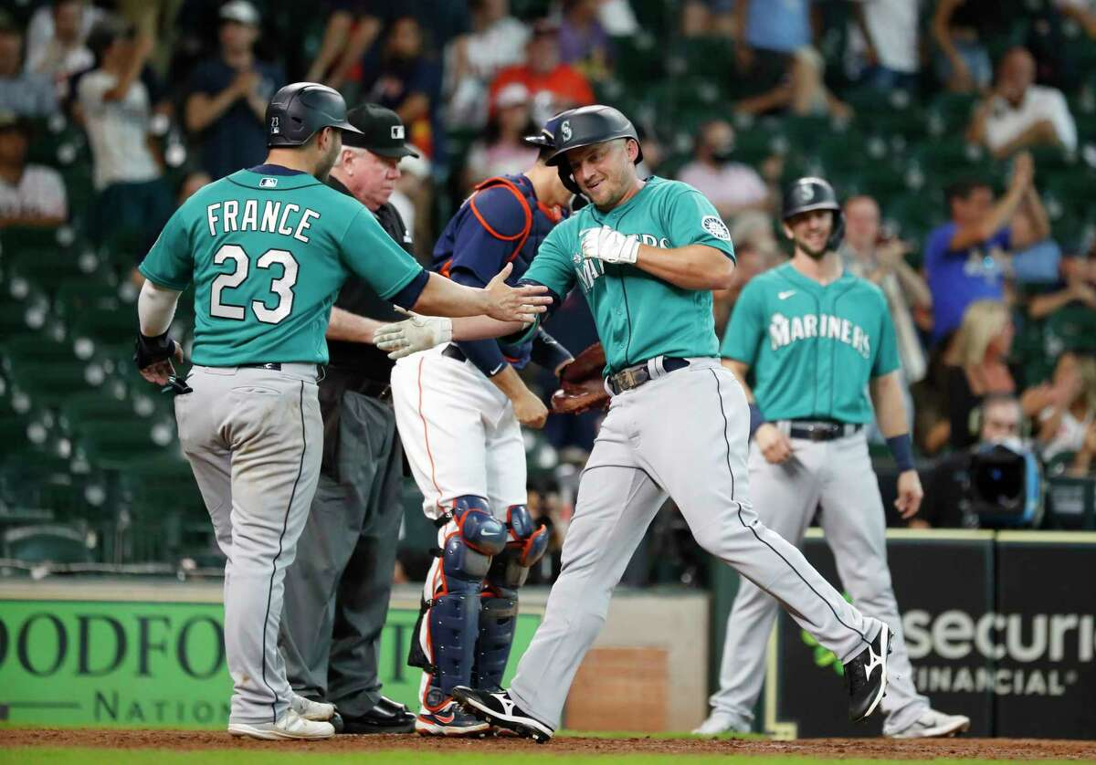 Seattle Mariners Kyle Seager celebrates his three-run home run off Houston Astros Ryne Stanek with Ty France during the 11th inning of an MLB baseball game at Minute Maid Park, Sunday, August 22, 2021, in Houston.