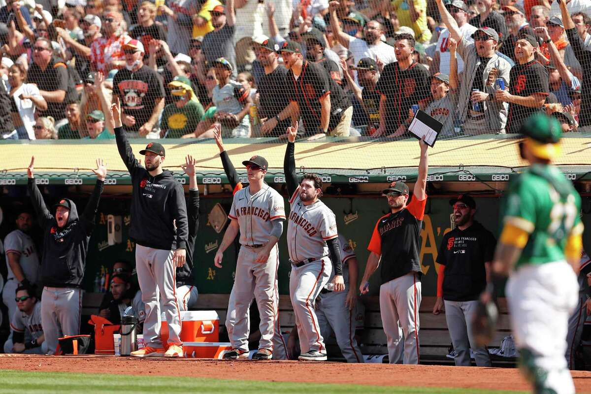 San Francisco Giants' dugout and fans react to Donovan Solano's 2-run go-ahead home run in 8th against Oakland Athletics' AJ Puk during MLB game at Oakland Coliseum in Oakland, Calif., on Sunday, August 22, 2021.