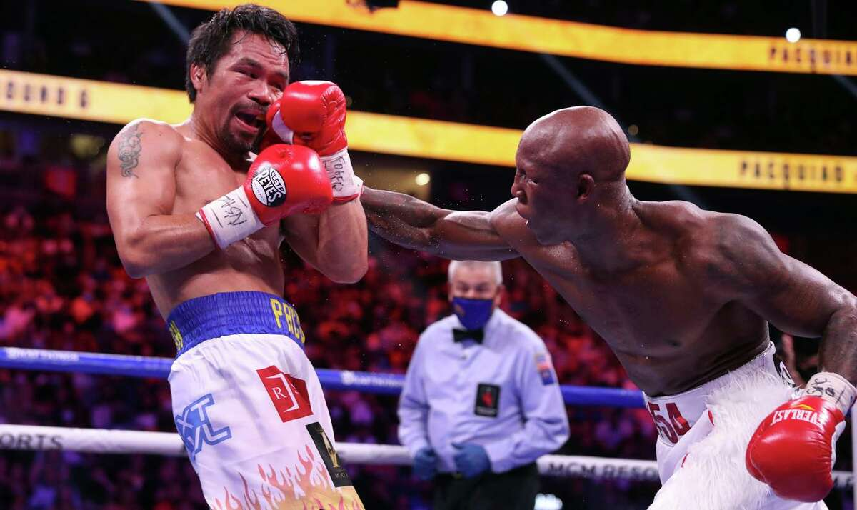Manny Pacquiao takes a punch from Yordenis Ugas during their WBA welterweight title fight in Las Vegas on Saturday. Ugas retained his title by unanimous decision.