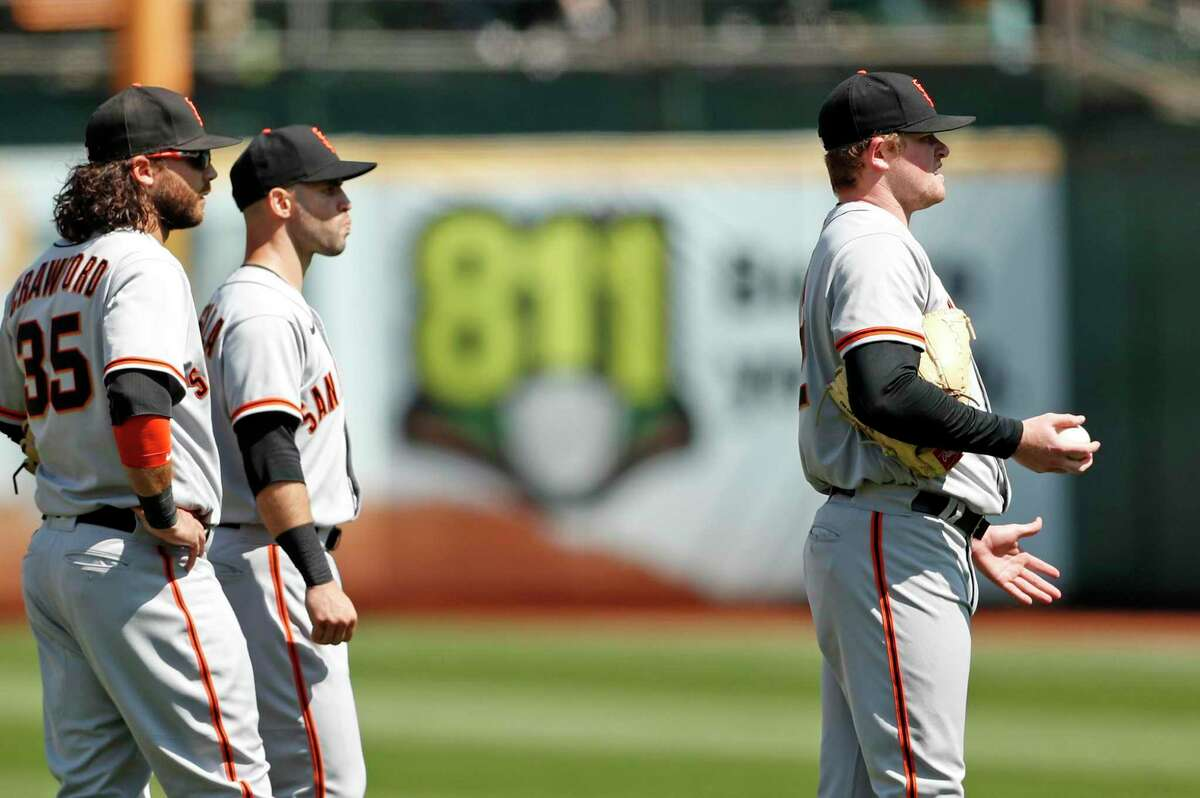 San Francisco Giants' Brandon Crawford, Tommy LaStella and Logan Webb wait for umpire's call after batted ball hit Mark Canha on base paths in 6th inning during MLB game at Oakland Coliseum in Oakland, Calif., on Sunday, August 22, 2021.