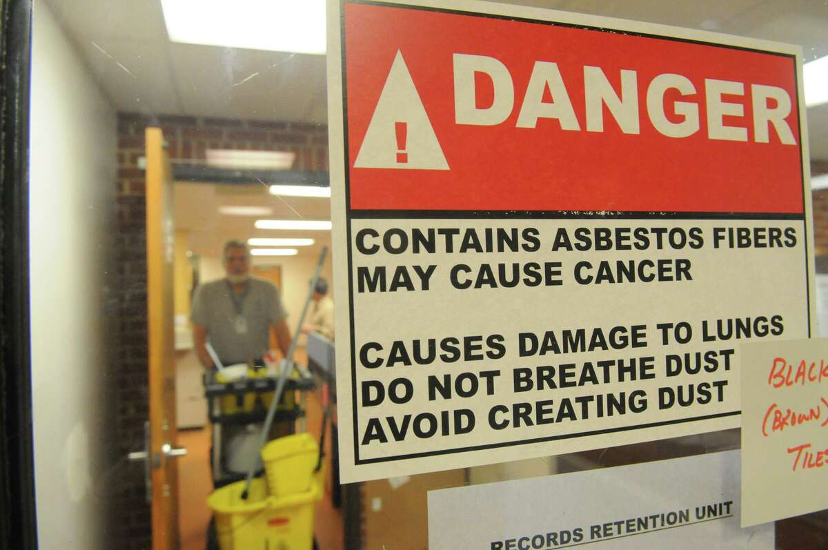 Signs warning of asbestos are posted throughout the Stamford Police Station in Stamford, Conn., Dec. 12, 2014.