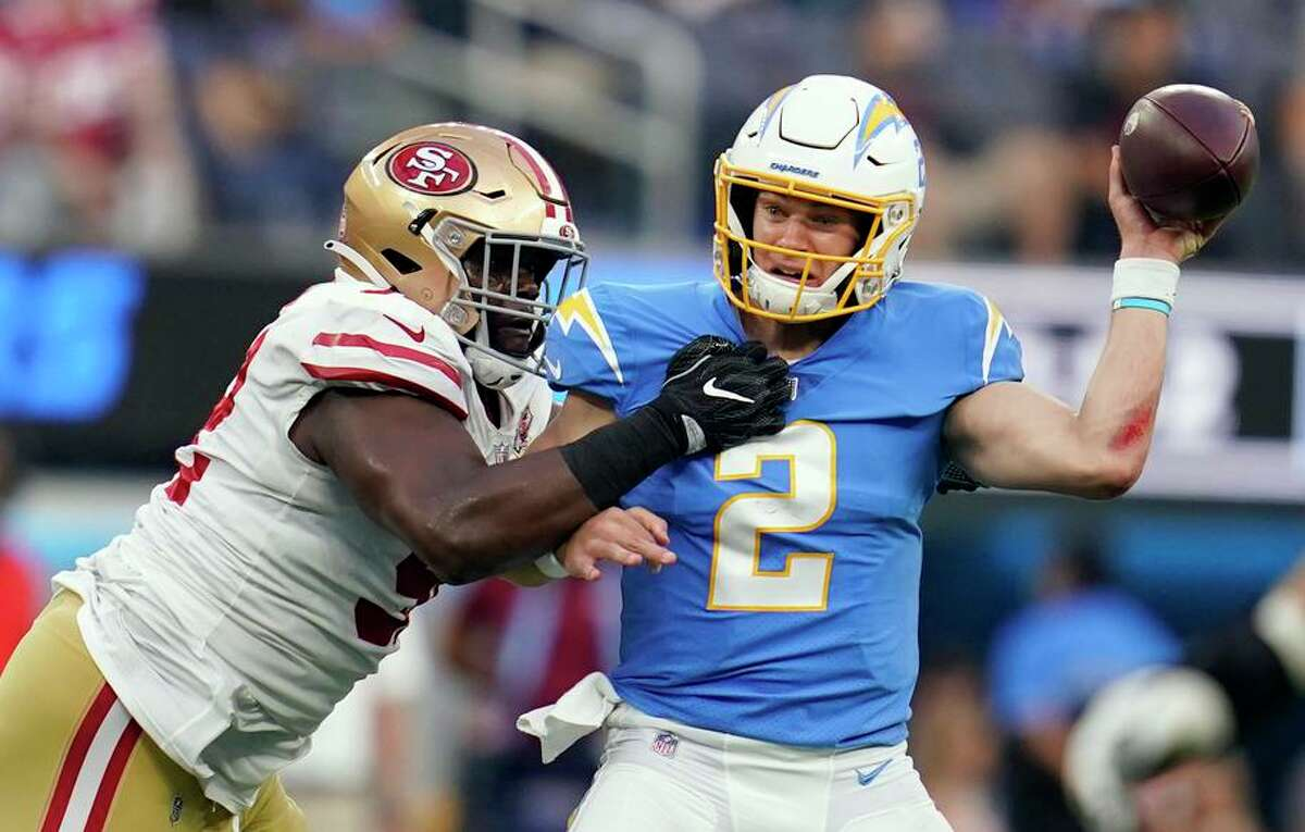 Los Angeles Chargers quarterback Easton Stick, right, is pressured by San Francisco 49ers defensive end Zach Kerr during the first half of a preseason NFL football game Sunday, Aug. 22, 2021, in Inglewood, Calif. (AP Photo/Ashley Landis)