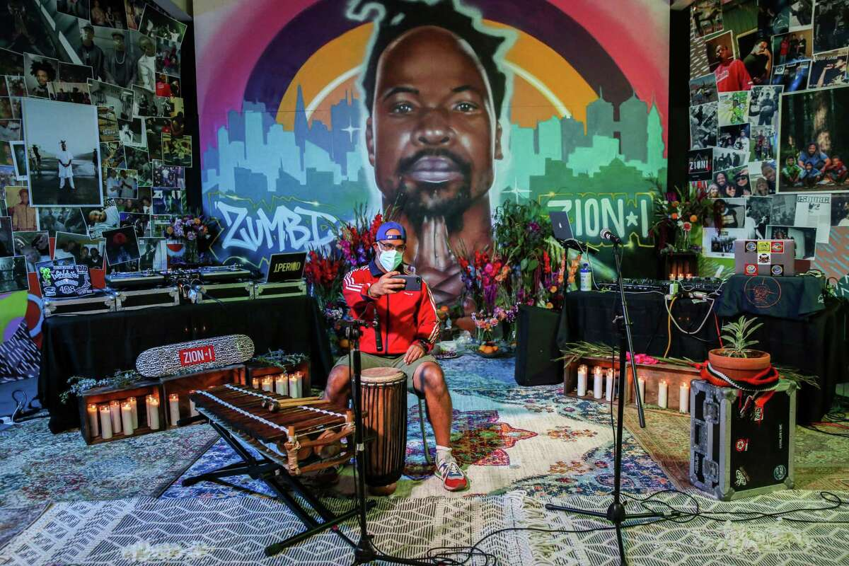 """School music director Guy De Chalus takes a selfie in front of a mural of Stephen """"Zumbi"""" Gaines before a celebration of his life in Oakland."""