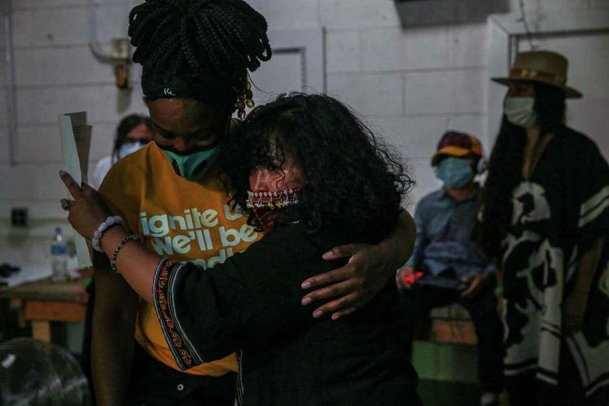 "Artist Jo ""love/speak"" Cruz (right) embraces a friend before a musical tribute and life celebration of beloved hip-hop artist Steve ""Zumbi"" Gaines in Oakland."