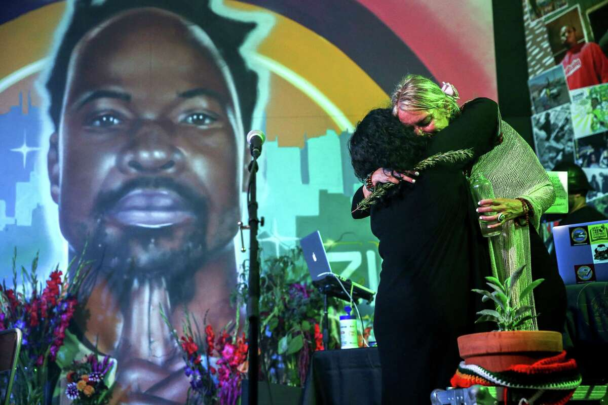 """Millaray Rodriguez Avila (right), partner of Stephen """"Zumbi"""" Gaines, embraces Jo """"love/speak"""" Cruz during a tribute to the hip-hop artist in Oakland. Gaines died this month at Alta Bates Summit Medical Center in Berkeley."""