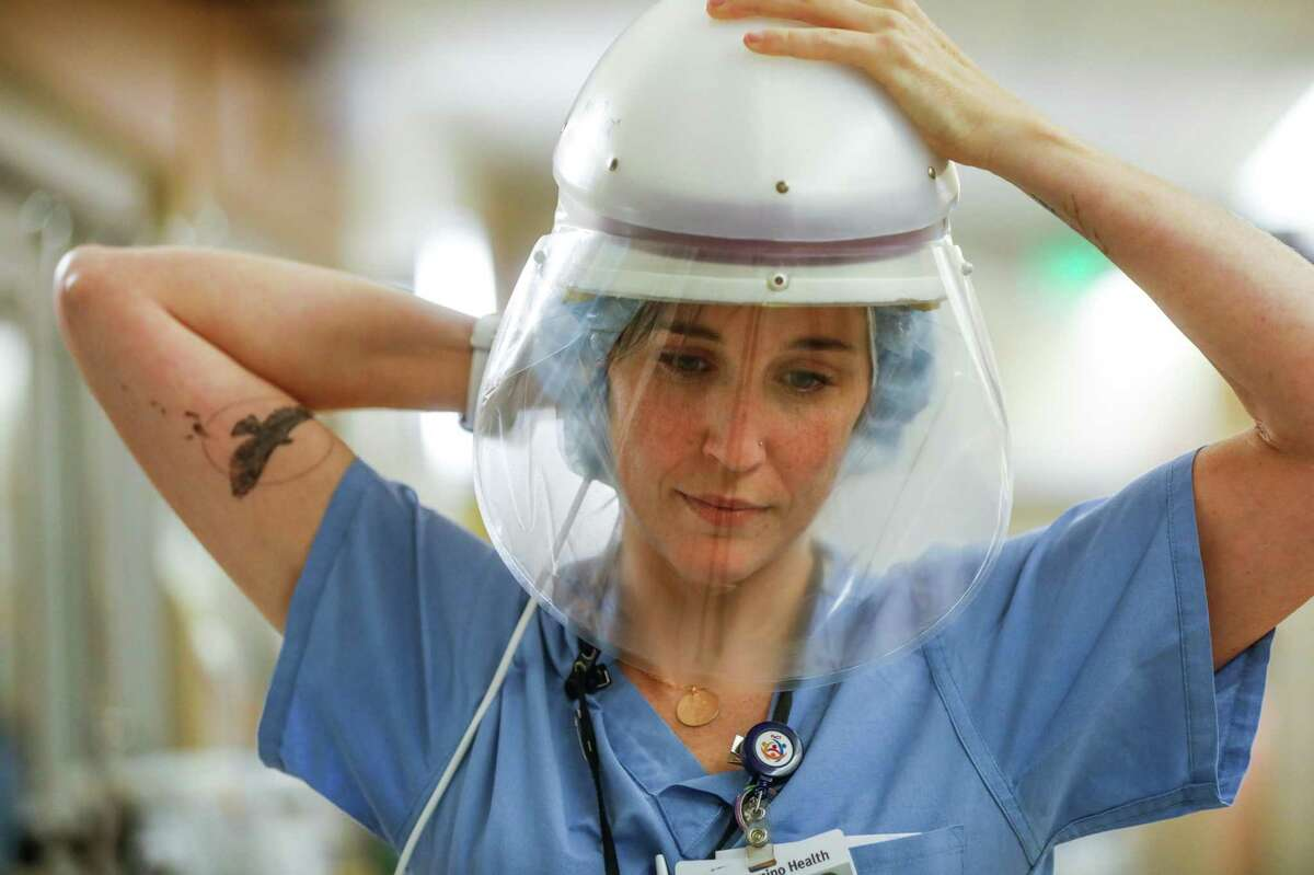 Nurse Shannon Baker dons protective gear before seeing a COVID-19 patient in an isolation room at El Camino Hospital in Mountain View.
