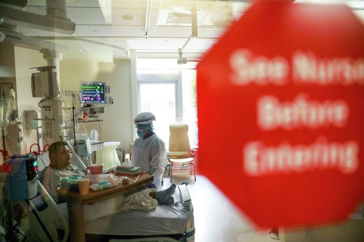 Nurse Meljan Tomas treats COVID-19 patient Juan Dominguezcruz at El Camino Hospital in Mountain View.