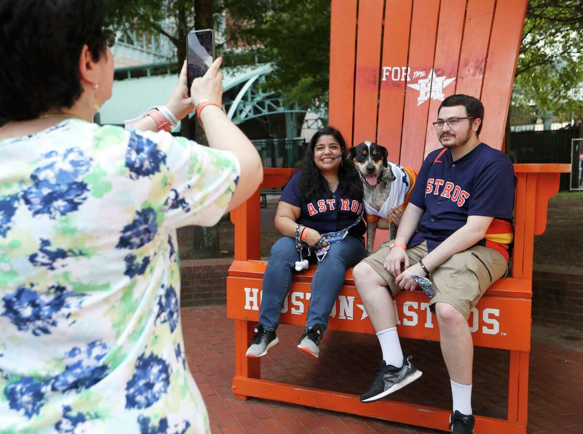 """Andrea Uresti and Sam Vengerik with """"Rocket"""" get their photos taken sitting in the giant Astros chair during Dog Day at the Park before the start of an MLB baseball game at Minute Maid Park, Sunday, August 22, 2021, in Houston."""