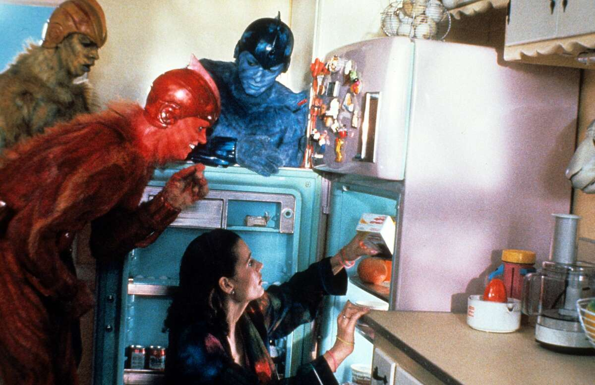 Damon Wayans, Jim Carrey and Jeff Goldblum hover around Geena Davis at the refrigerator in a scene from the film 'Earth Girls Are Easy', 1988.