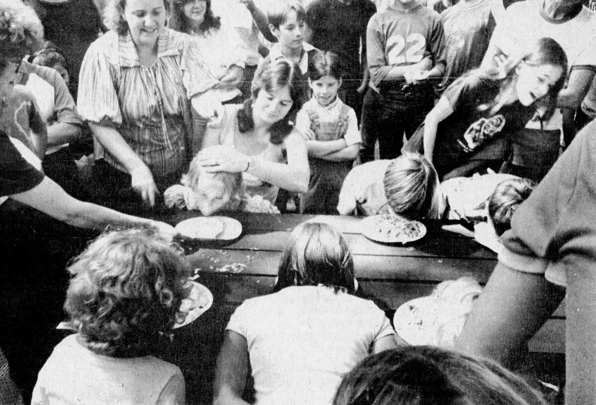 """These youngsters are getting more than their share of encouragement to become members of the """"clean plate club"""" as they take part in a food eating contest at Saturday's Wellston Fizzle celebration. The photo was published in the News Advocate on Aug. 24, 1981. (Manistee County Historical Museum photo)"""