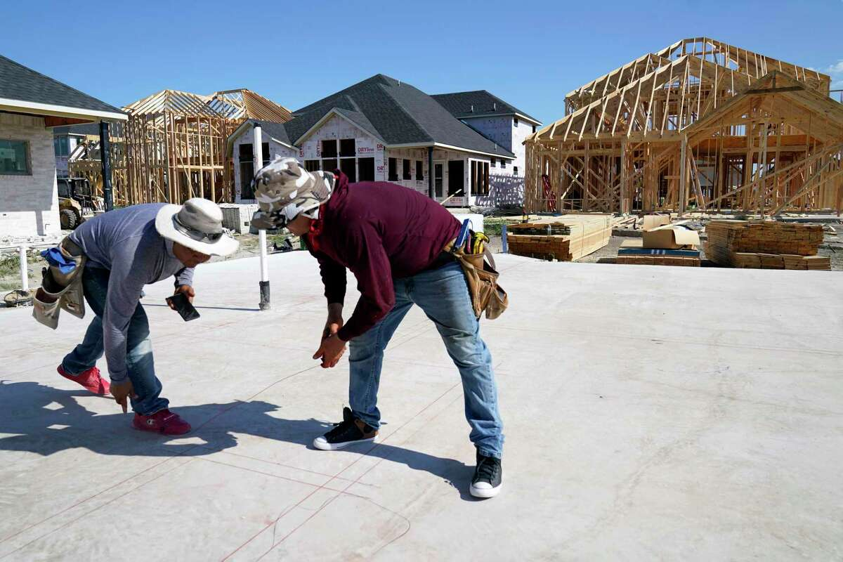 Elmer Romero, left, and Jorge Romero mark where walls will be erected in a home under construction in Allen. Texas is booming and its diversity is growing. Will that diversity be represented in redistricting?