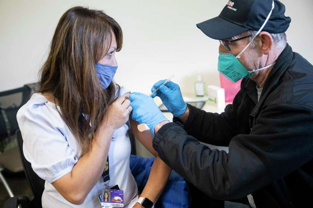 Redwood Christian School office administrator Grace John receives a dose of the Pfizer COVID-19 vaccine, which in February was being used under emergency approval, at a county mobile vaccination clinic in Hayward. The Pfizer vaccine now has been granted full approval from the FDA.