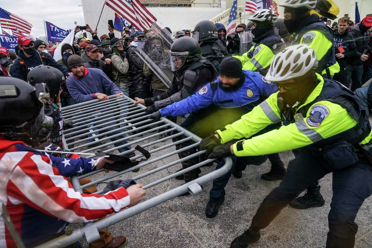 Violent insurrectionists loyal to former President Donald Trump hold on to a police barrier at the Capitol in Washington on Jan. 6, 2021.