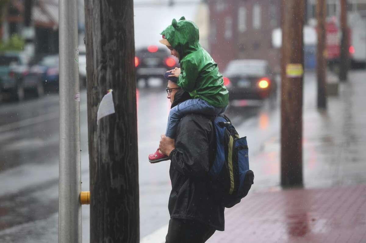 A father and child wait to cross River Street in downtown Milford during heavy rains from Tropical Storm Henri on Monday, August 23, 2021.