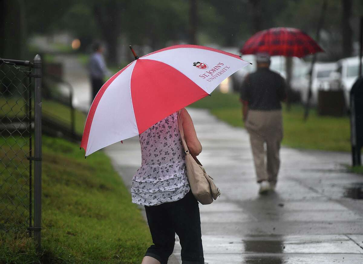 Umbrellas are the order of the day as remnants of Tropical Storm Henri continue to dump heavy rains on River Street in downtown Milford, Conn. on Monday, August 23, 2021.