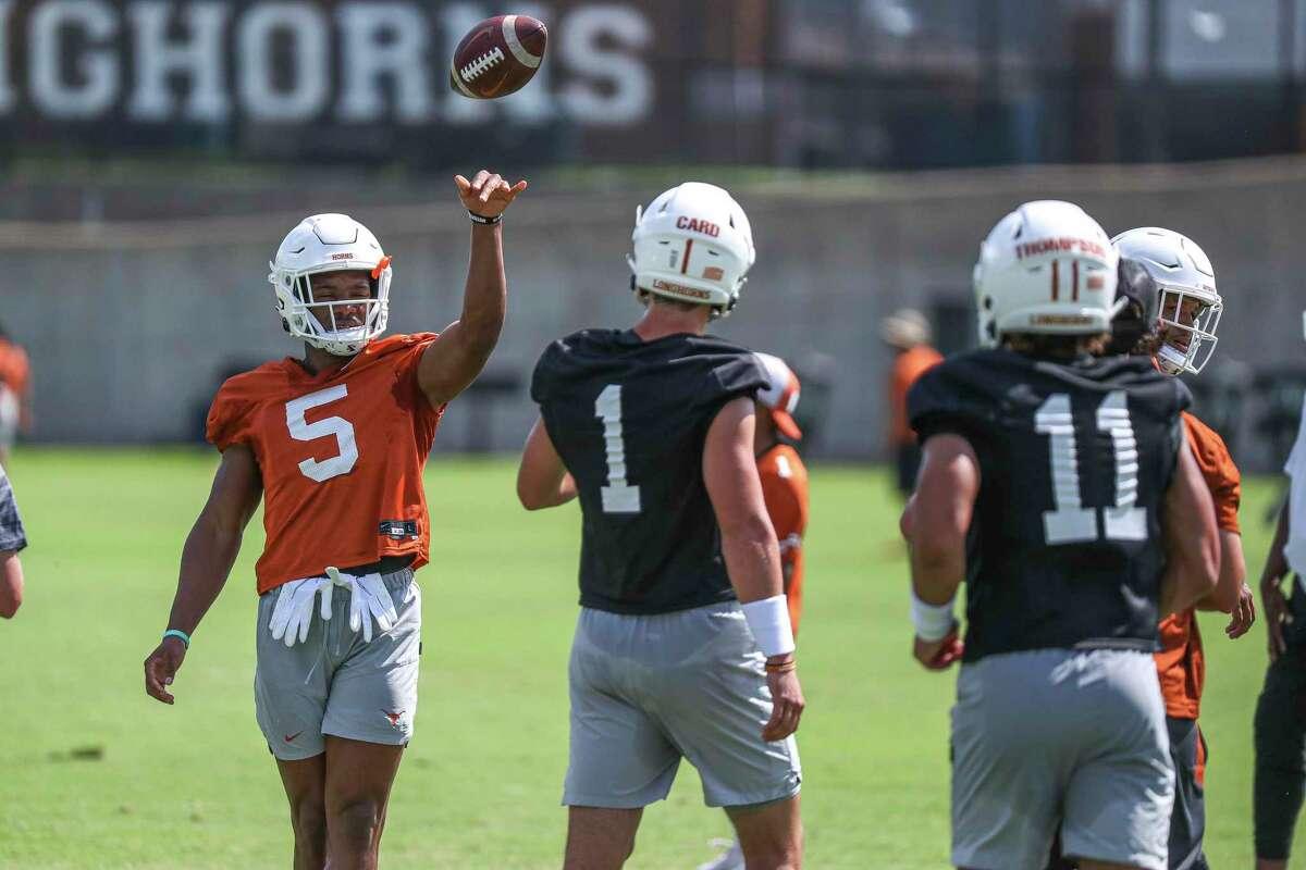 Texas running back Bijan Robinson throws the ball to quarterback Hudson Card during the NCAA college football team's practice Saturday, Aug. 7, 2021, in Austin, Texas. (Aaron E. Martinez/Austin American-Statesman via AP)