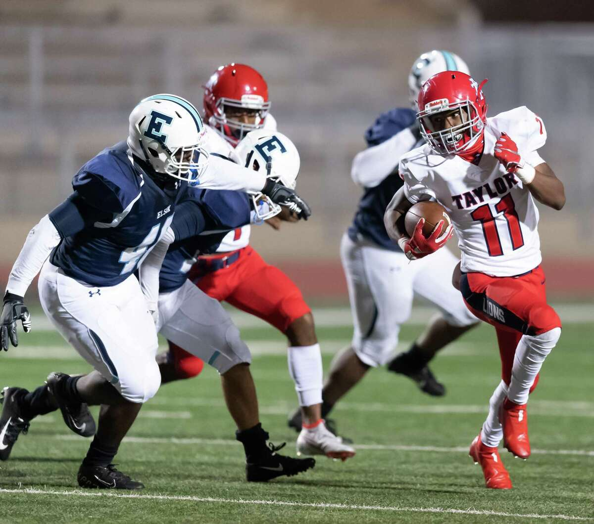 Danyren Williams (11) of the Alief Taylor Lions runs around left end in the second half against the Alief Elsik Rams during a High School football game on Friday, October 16, 2020 at Crump Stadium in Houston Texas.