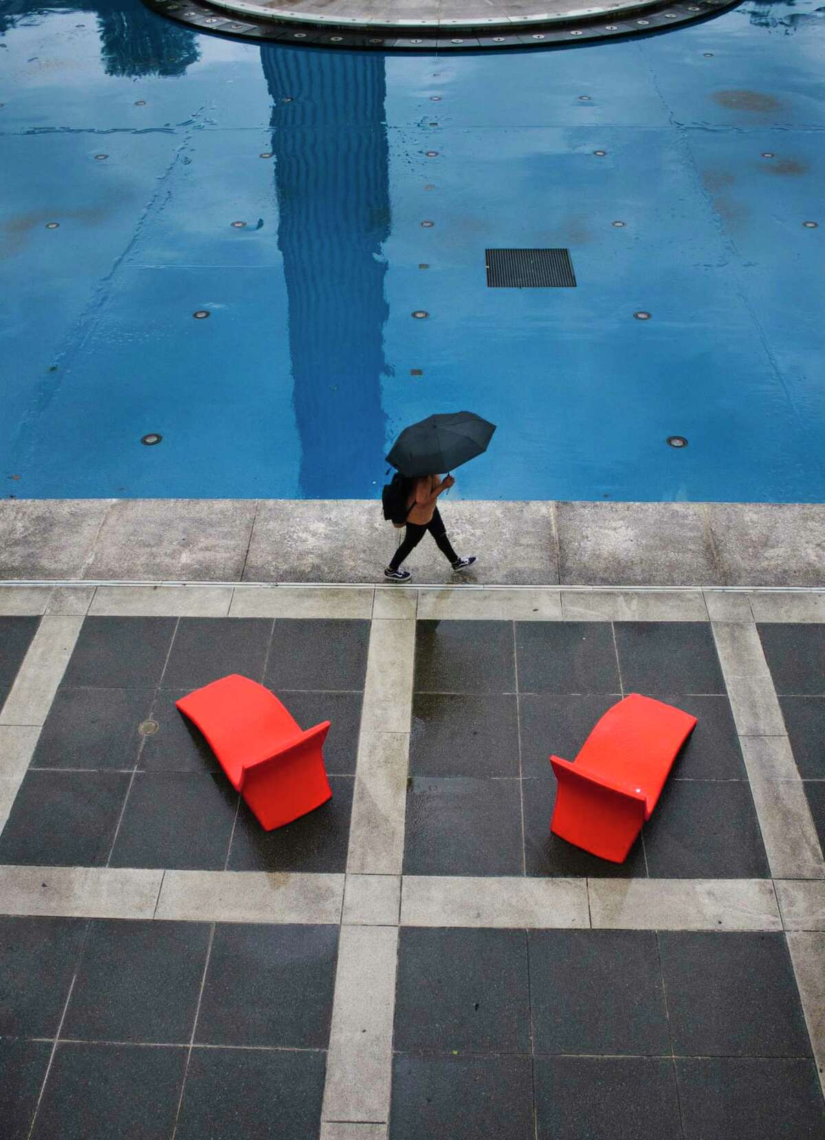 A University at Albany student walks through the campus in the rain on the first day of classes on Monday, Aug. 24, 2021, in Albany. The Food and Drug Administration's final approval Monday of Pfizer's COVID-19 vaccination triggered vaccination mandates at UAlbany and the rest of the state's SUNYcampuses.