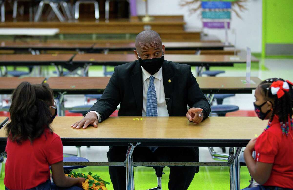 HISD superintendent Millard House II chats with two students at the cafeteria of Benbrook Elementary School, during the first day of school on Monday, Aug. 23, 2021, in Houston.