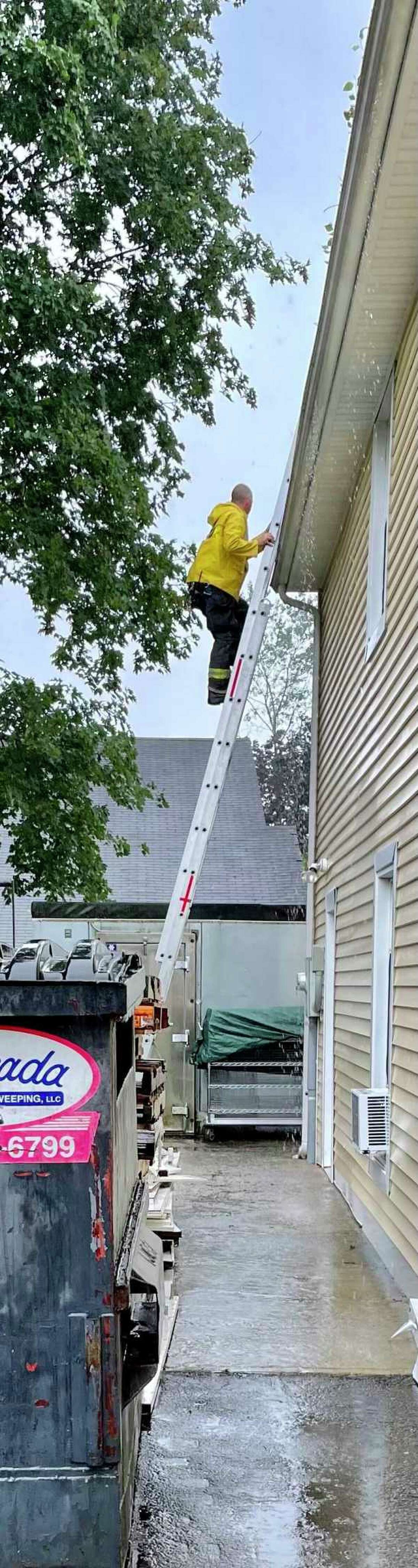 A member of the Torrington Fire Department climbs a ladder to clear a clogged gutter at Friendly Hands Food Bank Monday. Staff members discovered that the clogged gutter had caused flooding inside the building on King Street.