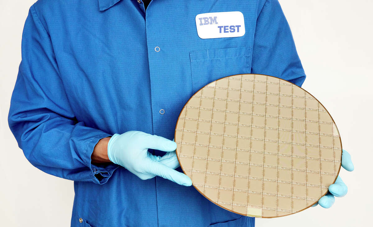An IBM worker holds a silicon wafer with embedded IBM Telum chips that were developed at Albany Nanotech and made in partnership with Samsung.