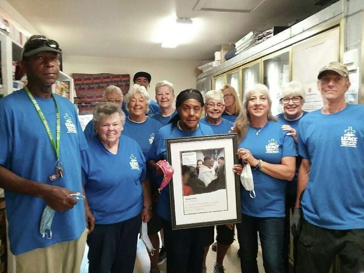 The team of Monday volunteers gather during last year's Crop Walk, to raise money to combat hunger. In the framed photo is a picture of the late Rev. Fr. Ron Schneider. (Courtesy photo)