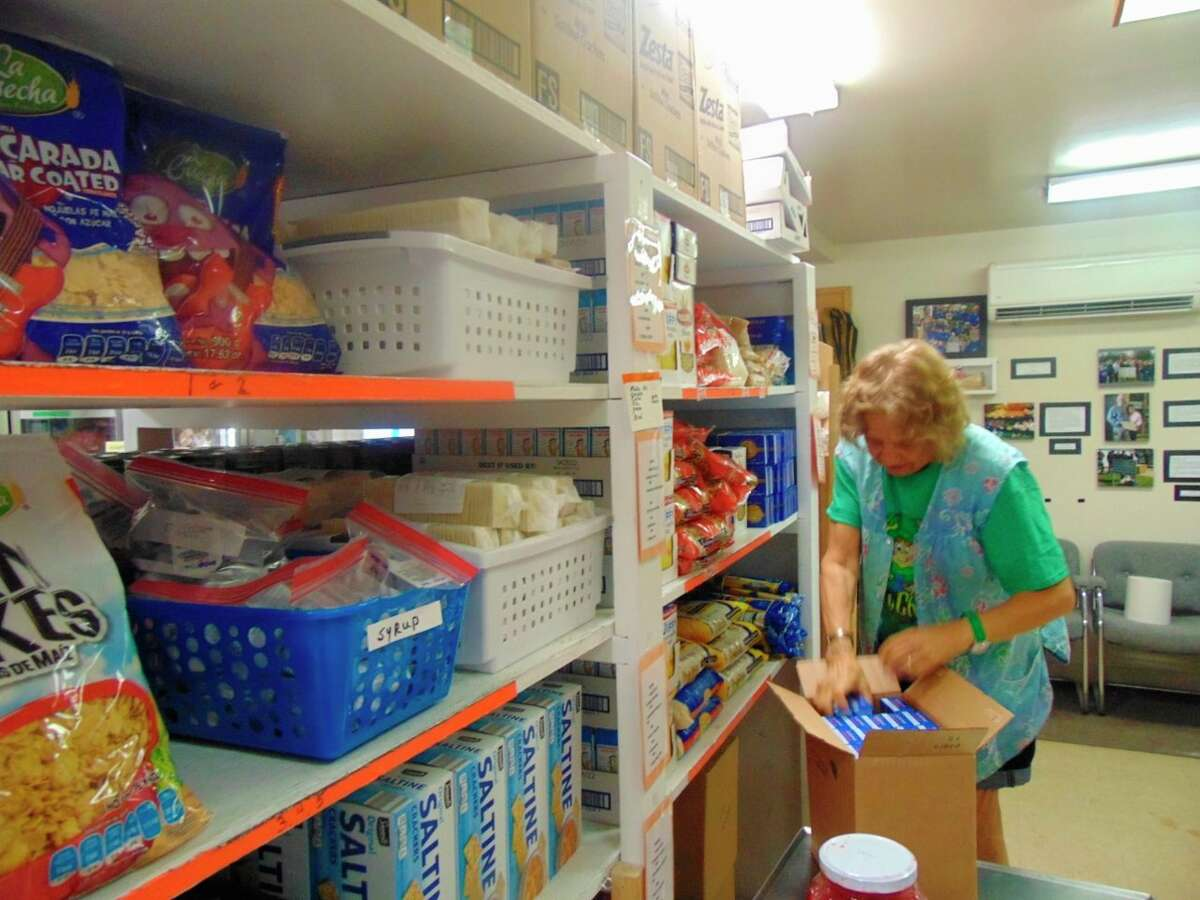 Volunteer, Marianne Cooke, who does the shopping for the pantry, helps stock shelves (Star photo/Shanna Avery)