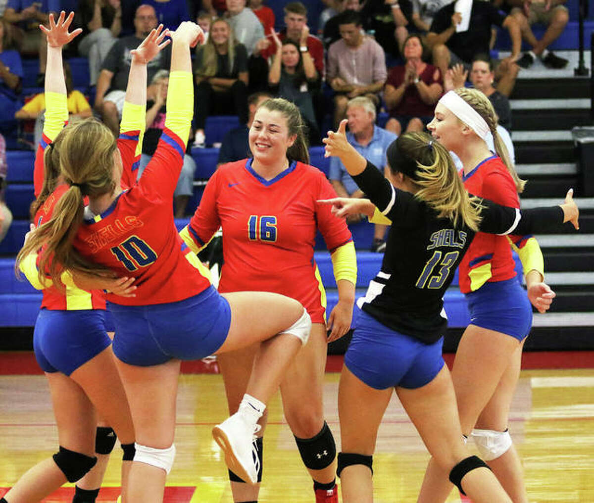 Roxana High School's Jacey Trask (16), Darcey McGuire (10), Makenzie Keller (13) and Reagen Stahlhut (right) celebrate a point with teammates in 2019 against Bunker Hill. Trask, who graduated from Roxana in May, has transferred to the Lewis and Clark Community College volleyball team after originally signing with John Wood College in Quincy.