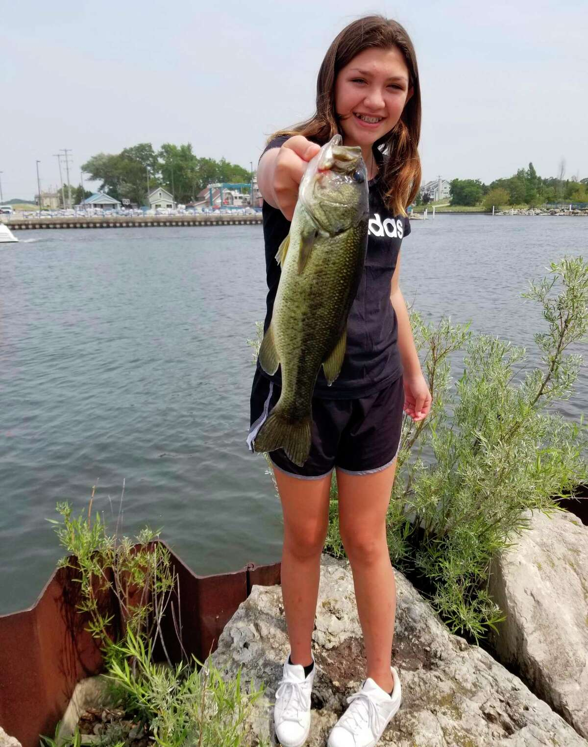 Madeline Dawson shows off the bass she caughtwhile participating in the Armory Youth Project's Fish On program. (Courtesy photo)