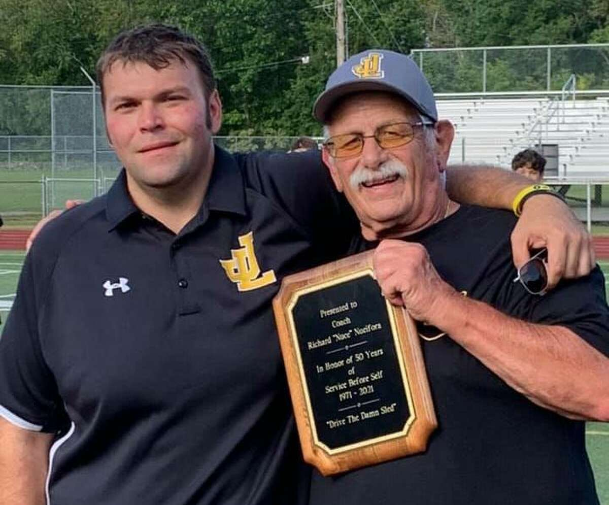 Law head football coach Chris Haley presents freshman coach Rich Nucifora with a plaque reflecting the 50th anniversary of when he began coaching football in Milford.